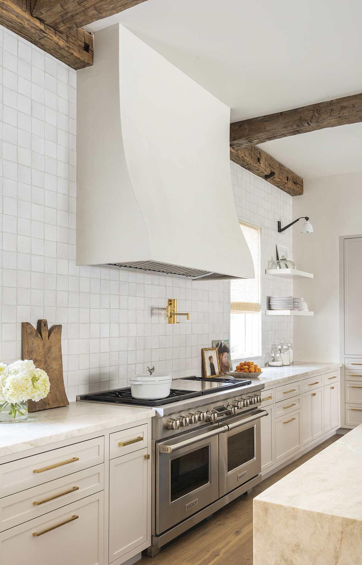 Bright bespoke kitchen design with view of stove and white vent