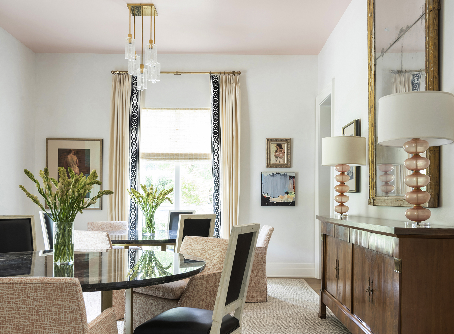 Well-lit bespoke dining room with pink accents