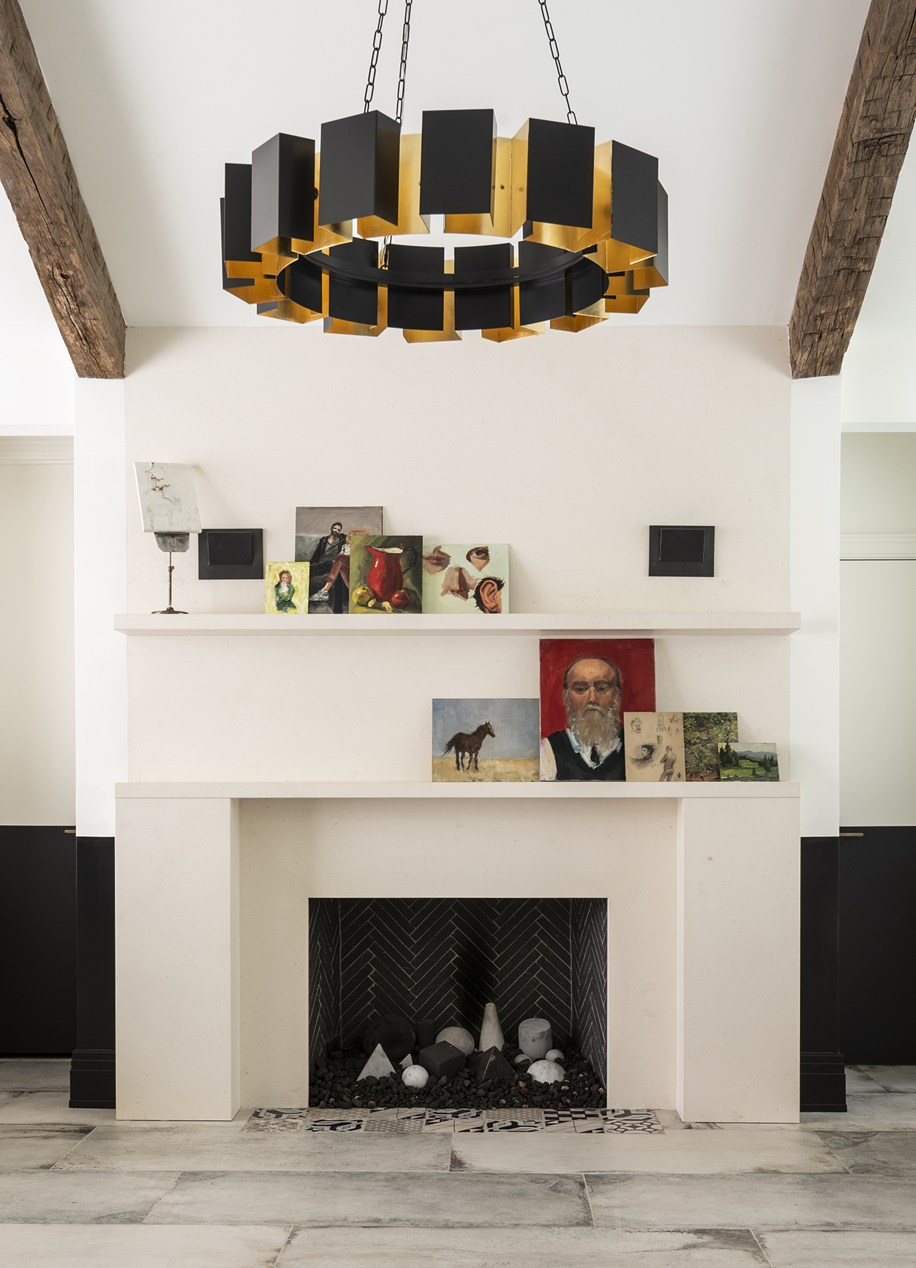 White walls and fireplace with curated paintings