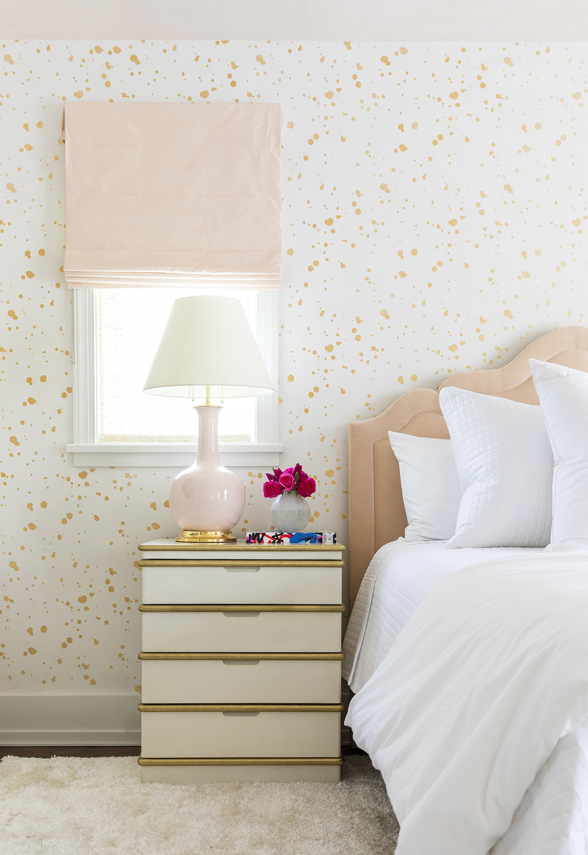 pink and gold bedroom with view of nightstand